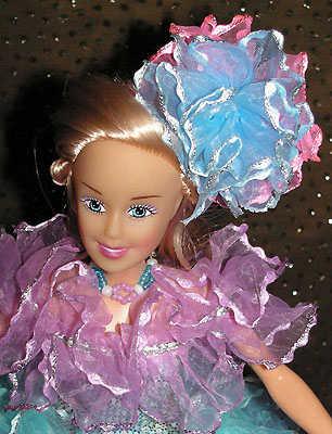 Голову украшает заколка из розово-голубых рюшей.  На руках плетеные из бисера браслеты, на шее ожерелье.