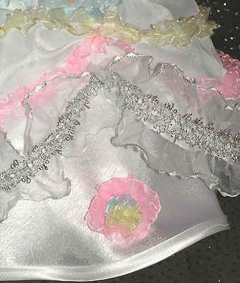 На голове - пышная заколка-резинка.  На руке - плетеный бисерный браслет.  Средняя юбка из белого атласа...
