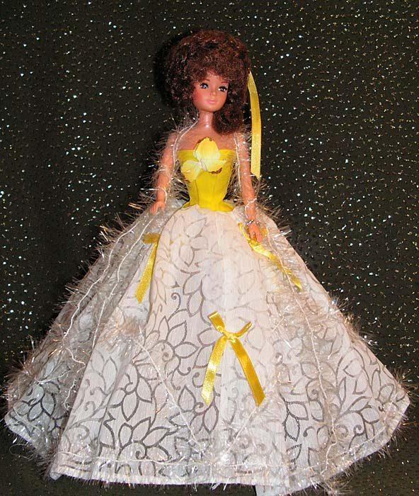 На Бетти платье с лифом желтого цвета и пышной белой полупрозрачной длинной юбкой из капроновой ткани с рисунком.